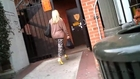Blonde lady in gray-brown pull over blouse, camouflage pants and yellow open toed high-heeled pumps